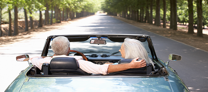 Elderly couple driving convertible